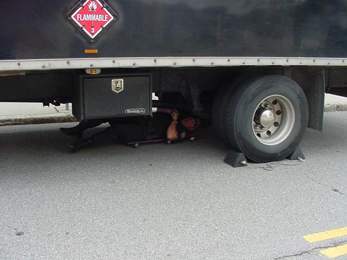 A police officer inspecting the bottom of a truck.